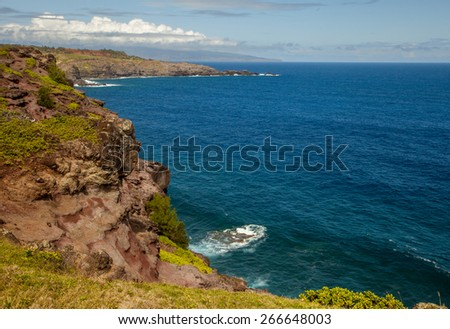 Mountain landscape with the pacific ocean in the background, island Maui, Hawaii. Composition of natural background, bright green grass and blue sky with clouds - stock photo