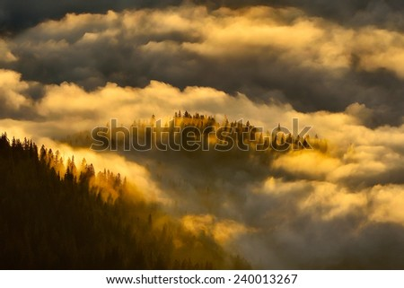 mountain landscape with thick clouds at sunset/sunrise - stock photo