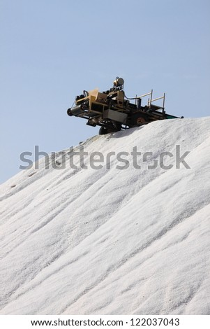 Mountain of salt and industrial equipment for marine salt production - stock photo