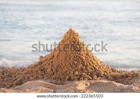 Mountain of sand on the beach - stock photo