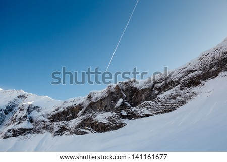 Mountain Peak and Airplane Trail near Megeve in French Alps, France - stock photo