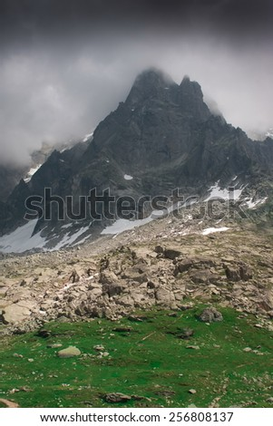 mountain peak in rain clouds and green sunny valley beneath  - stock photo