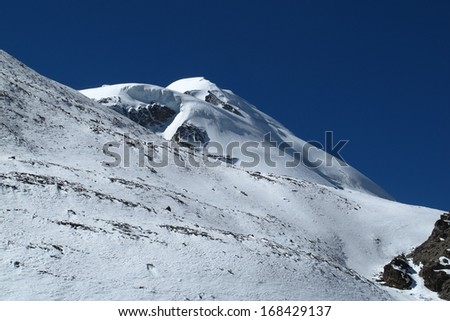 Mountain peak next to Thorung La Pass covered by glaciers and snow - stock photo