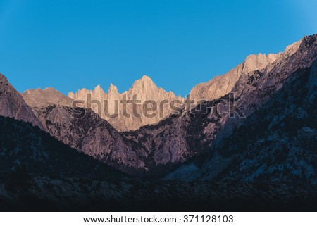 Mountain peaks against a clear blue sky background. - stock photo