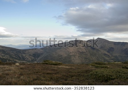 Mountain peaks in the autumn evening sky with clouds - stock photo