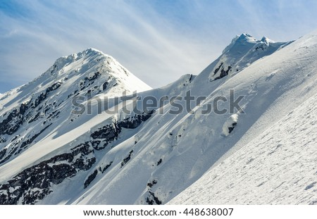 mountain peaks in winter time with clouds - stock photo
