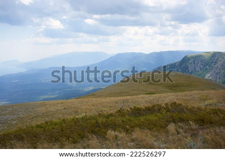 Mountain plateau and remote ranges in blue mist. - stock photo