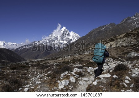 Mountain porter carrying heavy load in Himalayas, Nepal - stock photo
