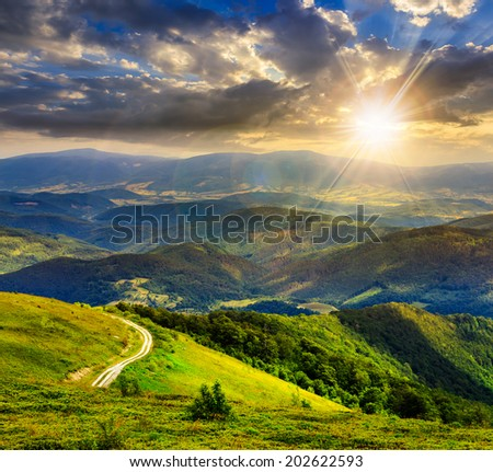 mountain range summer landscape. valley with stones and road on the hillside. forest on the mountain under the beam of light falls on a clearing at the top of the hill at sunset - stock photo