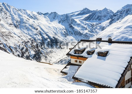 Mountain refuge hut covered with snow and peaks of Austrian Alps in background, Riffelsee ski resort in Pitztal valley - stock photo