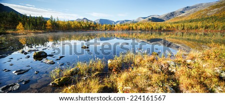 Mountain ridge panorama reflected in shallow Polygonal freshwater lake with bog hummocks in foreground, Hibiny mountains above the Arctic Circle, Russia - stock photo