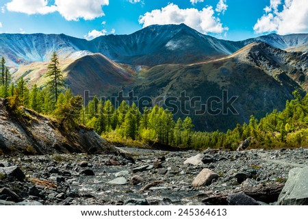 Mountain river at the foot of the ridge colored in a sunny summer day - stock photo
