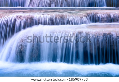 Mountain river background with small waterfalls in tropical forest. Clean blue water flows on cascades of Erawan park in Thailand - stock photo