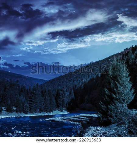 mountain river with stones the forest near the mountain slope at night - stock photo