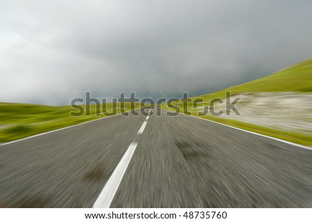 Mountain road blurred under stormy clouds - stock photo