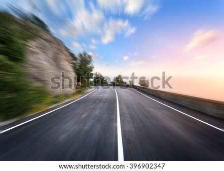 Mountain road in motion blur effect at sunset. Asphalt highway - stock photo
