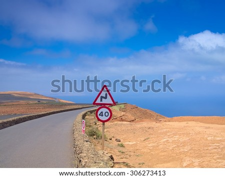 Mountain road in the blue sky against a background of ocean. Speed limit sign. Mirador del Rio, Lanzarote, Canary Islands, Spain - stock photo