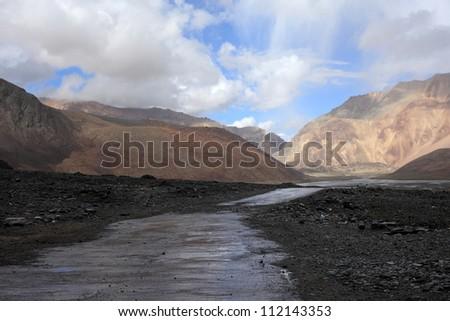 Mountain road under Himalaya mountains - stock photo