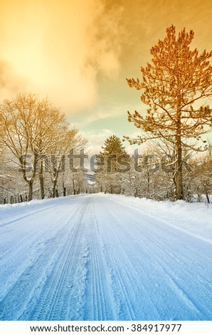 Mountain road with snow in winter at sunset - stock photo