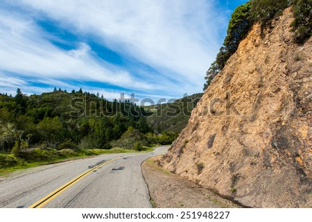 Mountain road with steep walls and a double yellow line - stock photo