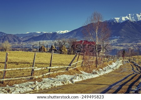 Mountain rural scenery with traditional Romanian farm and muddy country road during winter in the valleys of Bucegi mountains, Brasov county, Romania. - stock photo