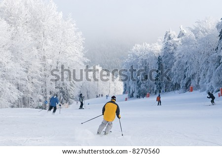 Mountain ski rider in yellow jacket on ski slope - stock photo