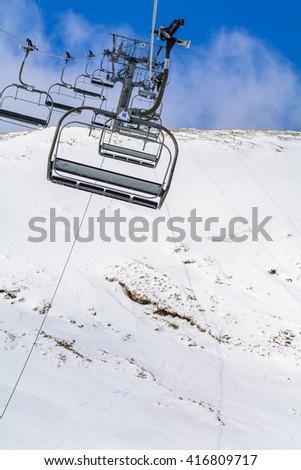 Mountain slopes with chairlift on a winter sunny day Winter mountains panorama with ski slopes and ski lifts near Brasov ski center, Romania. - stock photo