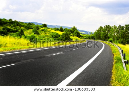Mountain spring road - stock photo