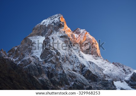 Mountain top at sunrise. Mount Ushba, Svaneti, Georgia, Caucasus. The first rays of the sun. Beauty in nature - stock photo