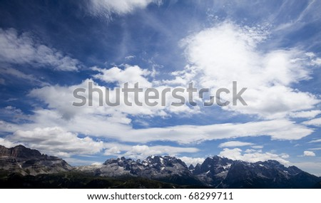 Mountain top under the blue sky with clouds - stock photo