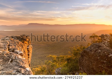 Mountain top views looking out over valley plain below in sunset light - stock photo