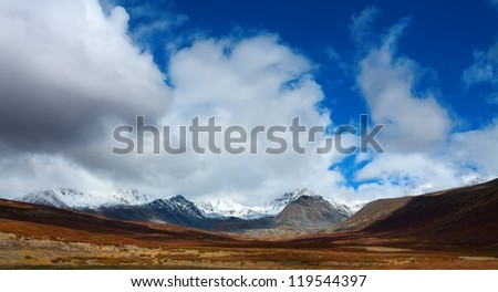 mountain top with snow and ice. Clouds over a glacier in autumn day. - stock photo