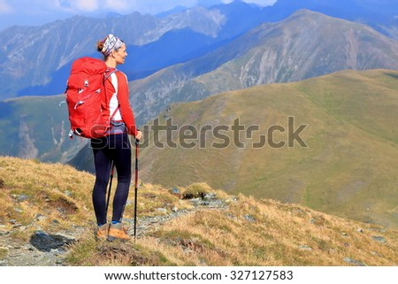 Mountain trail with woman backpacker in sunny day - stock photo