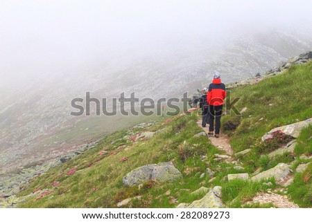Mountain trail with young mother and son embedded in thick fog - stock photo