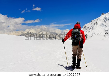 Mountain trekker looking at high winter Himalayas mountains, Nepal - stock photo