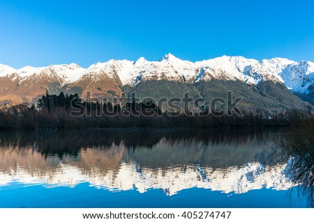 Mountain valley view. Nature landscape background photo of snow covered mountains reflected in blue water, Otago, New Zealand. Beautiful  mountain valley winter landscape - stock photo