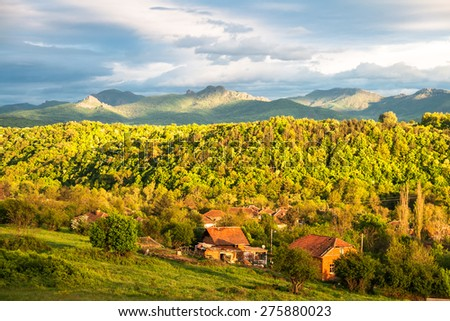 Mountain village at sunset in spring with the Balkan mountain range in the back - stock photo