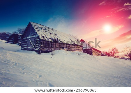Mountain winter landscape.View of the old farm. Fantastic evening glowing by sunlight. Retro filter.  - stock photo