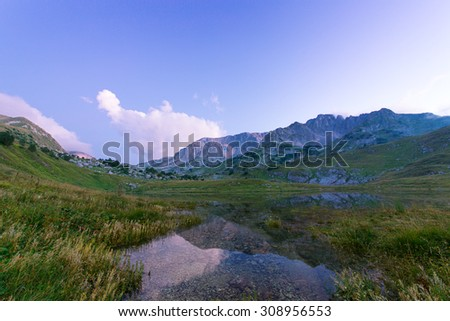 mountain with lake under blue sky - stock photo