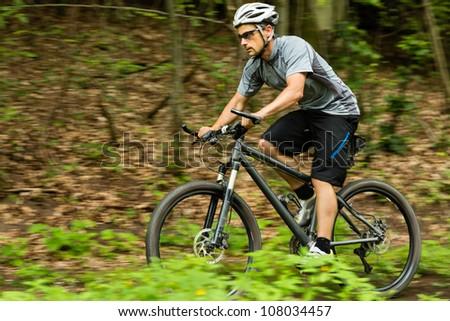 mountainbiker downhill on a trail - stock photo
