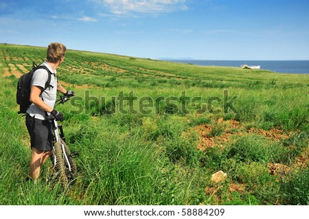 Mountainbiker observing beautifull nature with ocean in background - stock photo