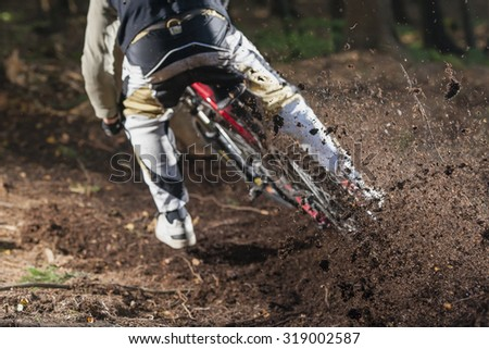 Mountainbiker rides on forest path - stock photo