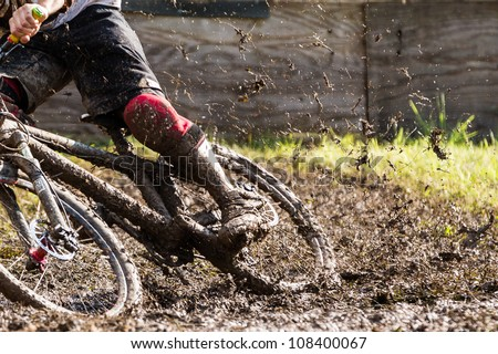 mountainbiker with a lot of mud - stock photo