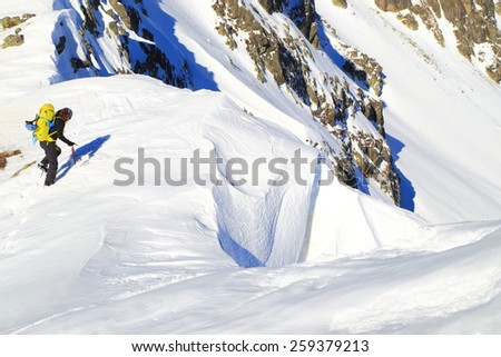 Mountaineer approaching the edge of snow covered ridge in sunny winter day - stock photo