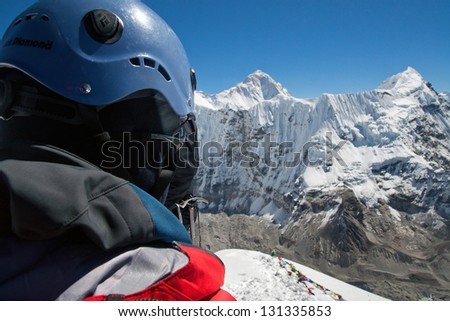 Mountaineer at summit looking out over mountain range - stock photo