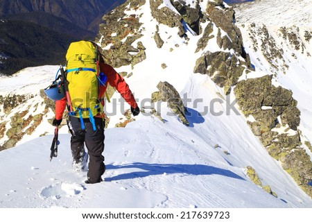 Mountaineer carries a backpack and climbing gear on snowy alpine route - stock photo