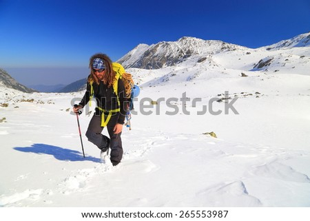 Mountaineer carries a backpack on snow covered trail  - stock photo