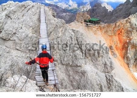 Mountaineer crossing the suspension bridge on Monte Cristallo, Dolomite Alps, Italy - stock photo
