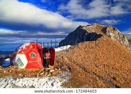 Mountaineer exits red refuge on the mountain ridge - stock photo