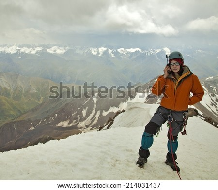Mountaineer is talking on phone - stock photo